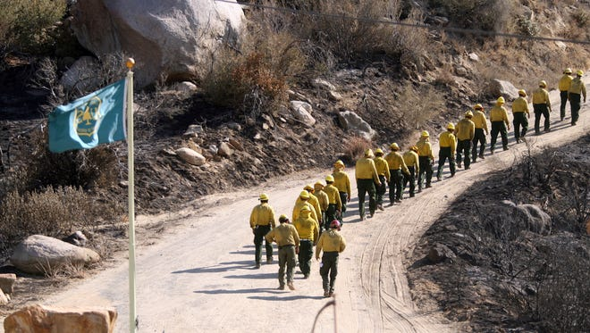 A U.S. Forest Service fire crew from Sequoia National Forest walk along a dirt road above the Banning pass on Sunday, August 11, 2013, on their way to visit the site where five U.S. Forest Service firefighters were killed fighting the October 2006 Esperanza Fire.