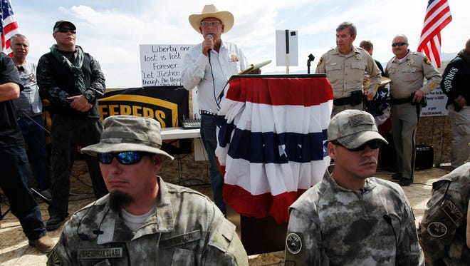 Rancher Cliven Bundy, middle, addresses his supporters along side Clark County Sheriff Doug Gillespie, right, on April 12, 2014.