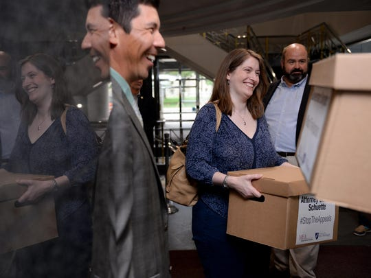 MEA Board of Directors member and Novi teacher Tom Brenner, center, and Hamtramck teacher Michelle Cook deliver a box of petition signatures to Gov. Rick Snyder's office in the George W. Romney Building on Thursday, June 23, 2016.