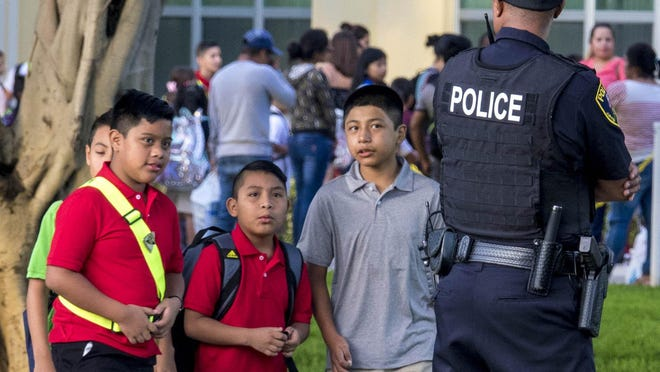 Students walk to classes past Jupiter and school district police during the first day of classes Monday at Jupiter Elementary School.