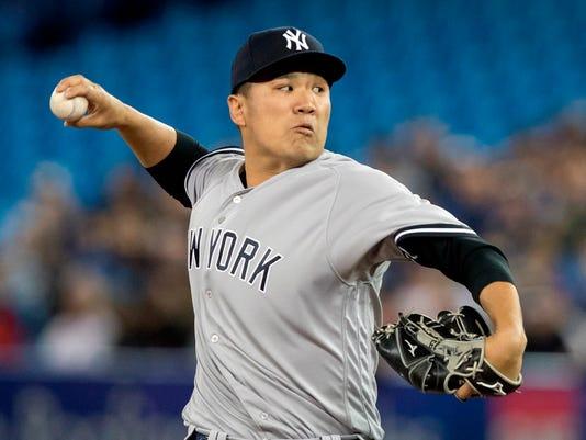 New York Yankees starting pitcher Masahiro Tanaka throws against the Toronto Blue Jays.