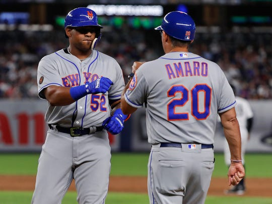 New York Mets' Yoenis Cespedes (52) is congratulated by first base coach Ruben Amaro Jr (20) after hitting a single to right field against the New York Yankees during the sixth inning of a baseball game Friday, July 20, 2018, in New York.