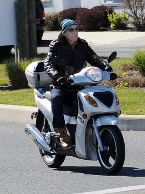 Scooter riders drive around Downtown Rehoboth Beach.