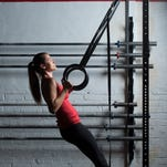 Kristin Rance works the rings during an Olympic weight-lifting class at District CrossFit in Washington in October; increasingly, women who work out do it for muscle definition.