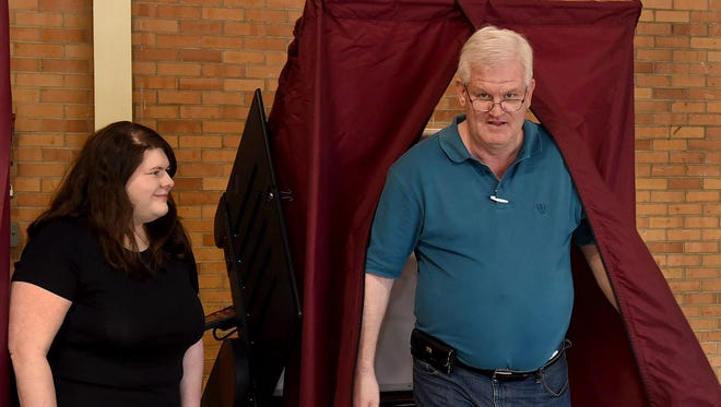 Doug Sandoz exits the voting booth after casting his vote in Saturday's election. A two-part, parish-wide tax proposition overwhelmingly failed to pass.
