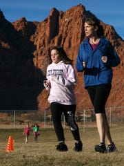 Melissa Miller, right, a Girls on the Run coach and the executive director of Girls on the Run Southern Utah, runs with program participants as they circle the playground at Vista Elementary School in Ivins Wednesday, Jan. 27, 2016.