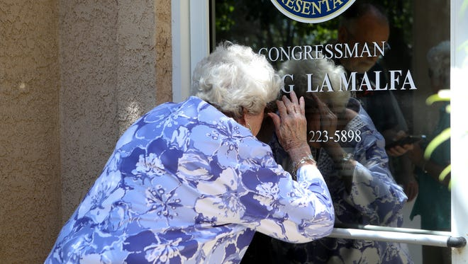 Elaine Clanton looks into Congressman Doug LaMalfa's Redding office Friday. Clanton and others were attempting to to deliver a card and cupcakes to the office in celebration of the birthday of Medicare, Medicaid and Social Security. The group later returned and delivered the items.