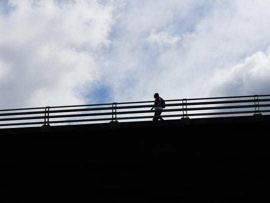 A man walks across the Madison Avenue bridge Wednesday,