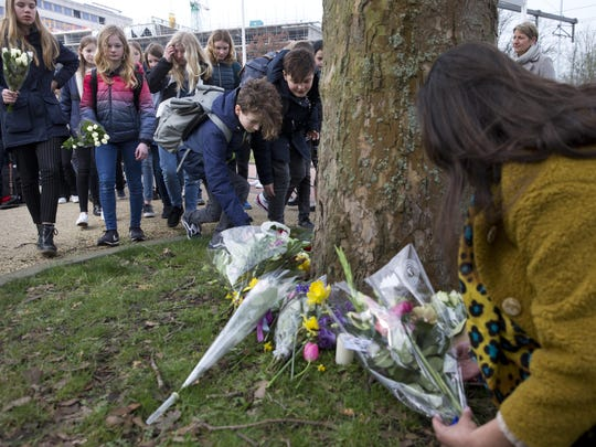 People lay flowers near the site of a shooting incident in a tram in Utrecht, Netherlands, Tuesday, March 19, 2019. A gunman killed three people and wounded others on a tram in the central Dutch city of Utrecht on Monday.
