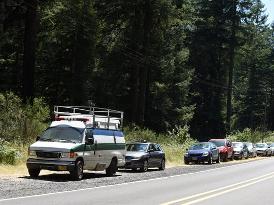 Cars are parked along the road near a swimming hole along the Little Fork of the Santiam River on Wednesday, July 1, 2015.