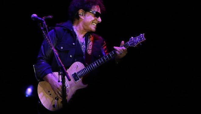 Journey founding guitarist Neal Schon smiles Monday night at the Resch Center in Ashwaubenon.