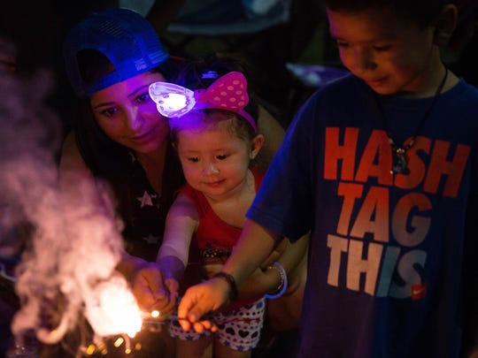 Veronica Hernandez, left, holds her daughter Sophia Vasquez, 2, as they light sparklers with David Florez, 5, along the route of the Electric Light Parade. Monday, July 3, 2017 at Apodaca Park.