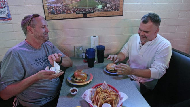 Roger (left) and Steven Ham eat lunch at Harvey's Wineburger in Phoenix in December 2010. The two dads find time together during Roger's lunch break from work and while their 12 adopted kids are in school.