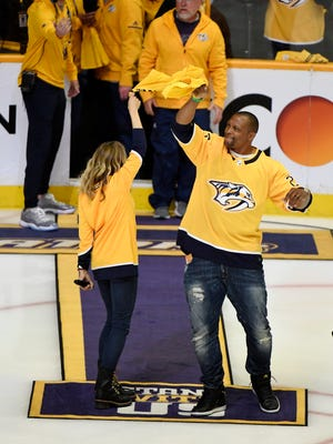 Former Titans star Eddie George and singer Sheryl Crow wave towels before Game 7 of the second round NHL Stanley Cup Playoffs at Bridgestone Arena, Thursday, May 10, 2018, in Nashville, Tenn.