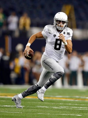 Jan 12, 2015: Oregon Ducks quarterback Marcus Mariota (8) runs with the ball against the Ohio State Buckeyes in the 2015 CFP National Championship Game at AT&T Stadium.