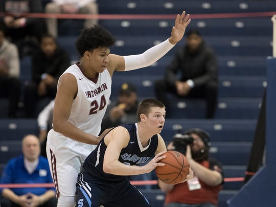 Shawnee's Dean Noll looks to pass the ball as he's covered by Don Bosco's Ronald Harper. Don Bosco vs Shawnee in NJSIAA boys TOC semifinal game in Toms River NJ on March 15, 2018
