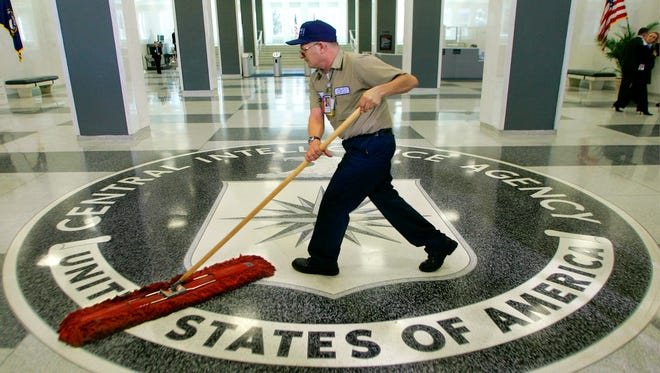 A workman quickly slides a dust mop over the floor at the Central Intelligence Agency headquarters in Langley, Va.