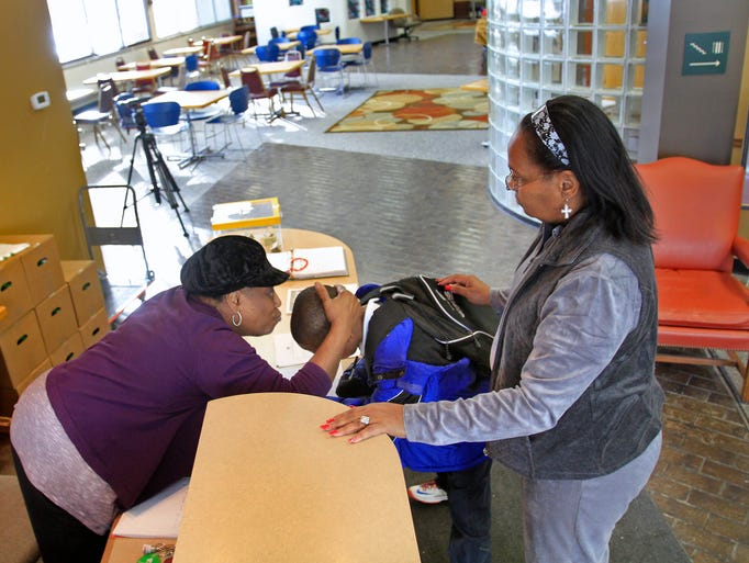 An after school program kid signs in and is greeted at the Martin Luther King Service Center at 40 W. 40th Street, Wednesday, February 20, 2014.  Kids who come for the program are picked up by the center's bus and brought to the center for the after school activities which include a warm meal.