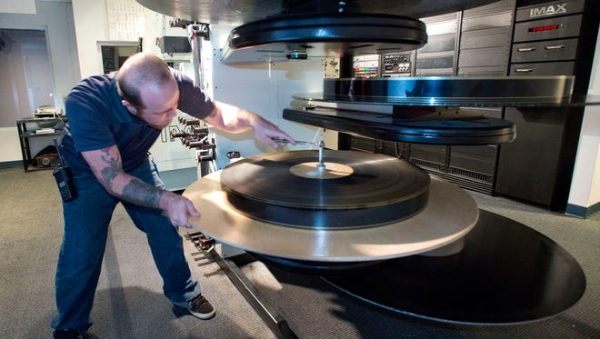 """Mike Moodispaugh, loads one of the last """"films"""" onto the IMAX projector at the National Naval Aviation Museum Thursday Dec. 31, 2015.  On Jan. 1st the museum will stop showing """"film"""" movies and convert to a new digital projection system. The process is expected to be complete in March 2016."""