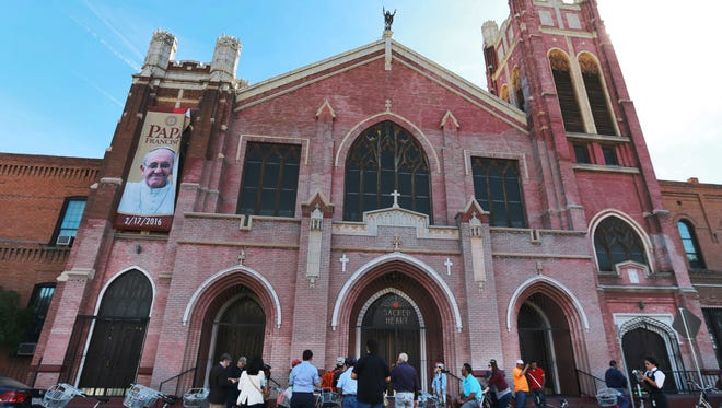 Segundo Barrio Bicycle Tour participants stopped to view Sacred Heart Catholic Church in March 2016.