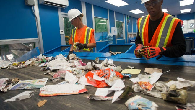 ECUA recycling center workers April Derry, left, and Jerry Foster look for non-recyclable materials on the sorting lines at the Beulah Landfill sorting facility.