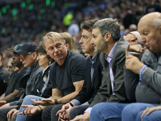 Bucks owner Wes Edens (center) talks with fans courtside