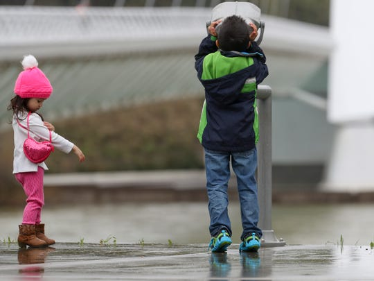 Alana Collins, 3, left, and her brother Nolan spend a wet afternoon at Turtle Bay near the Sundial Bridge. The two children and their family were visiting the area from Vacaville.