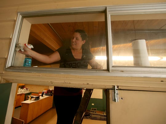 Lana Myers, an Olympic Mountain Rescue volunteer, washes windows at the former fire hall on Rocky Point Road on June 29.