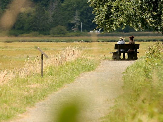 A pair sits on a bench in the closed trail portion of the Mary E. Theler Wetlands in Belfair on Monday.