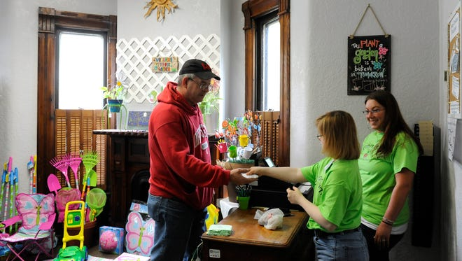 Jim Bowden takes his change from daughter, Janet, during her first day of work behind the counter with Ashley Skeens, director of Adult Day Services for the Center for Disability Services, at Green Dreams Boutique in Newark