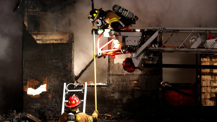 Firefighters work to extinguish a blaze at Casa Loma