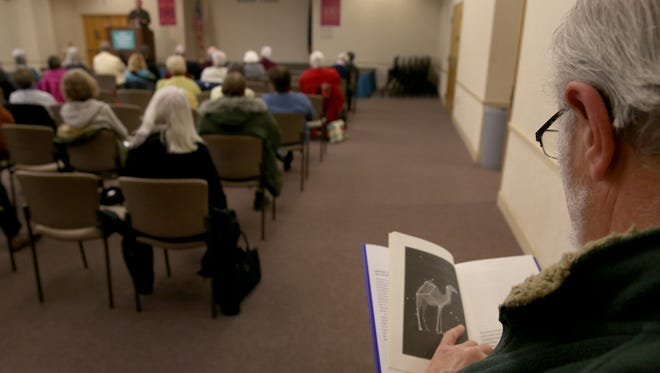 """Marty Steinhauser reads through  """"Only the Animal"""" during a book review by Jeff Wyatt at the Central Library's Books Sandwiched In."""