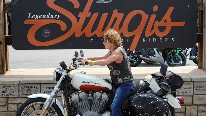 Rebecca Nance of Darnell, Arkansas rests for a moment in front of the Sturgis welcome sign on Aug. 4, 2018, following a two-day ride from home to the rally in South Dakota.