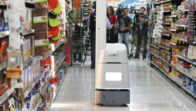 The Bossanova robotic scanner makes its way down an aisle Thursday in the Walmart store at 7101 Gateway Blvd. W. The device scans merchandise, collecting a variety of data that is downloaded to store associates.