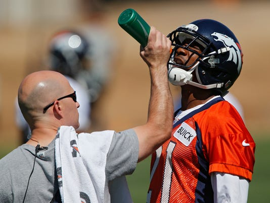 Denver Broncos cornerback Aqib Talib, right, gets a drink of water during an NFL football organized team practice at the Broncos training facility in Englewood, Colo., on Monday, June 2, 2014. (AP Photo/Ed Andrieski)