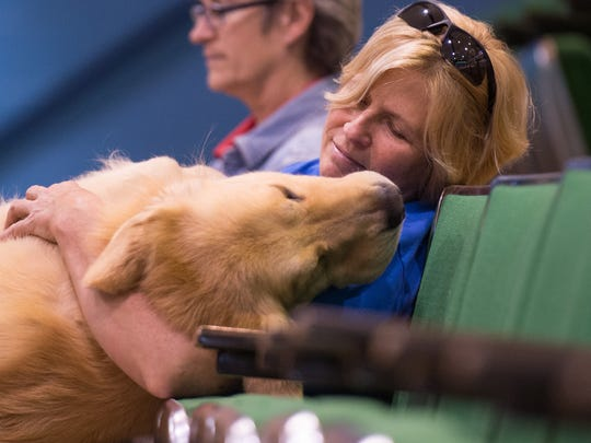Jenny Cochran, of Harleysville, Pa. relaxes in the bleachers with her 4-year-old Golden Retriever, Tracker, during the Eastern Shore Classic Dog show at the Wicomico Youth and Civic Center on Nov. 6, 2015.