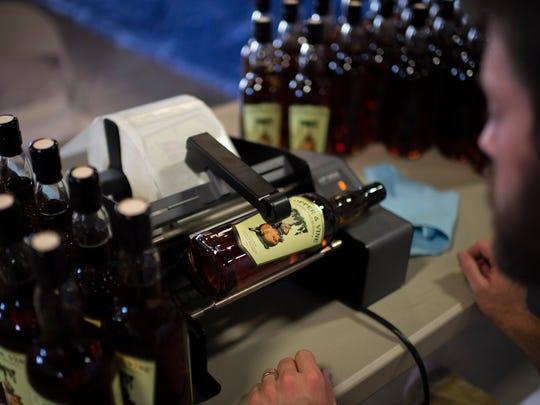 Chief distiller James Yoakum labels bottles of brandy last winter at the distillery in Camden.