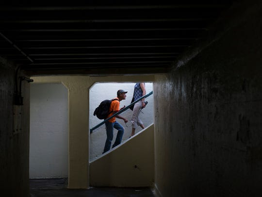 People enter and exit the 5th Street pedestrian tunnel Friday, June 1, 2018 in Philadelphia, Pa. The Delaware River Port Authority has hired  two artists to paint a mural inside it.
