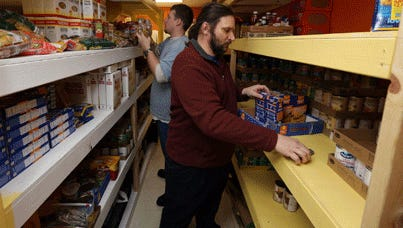 Gregg Eid, foreground, and Steven Klein stock food shelves at Community Action of Southeast Iowa in Burlington, Iowa. Anti-hunger activists say state food stamp cuts on top of earlier federal cuts are stressing food resources.