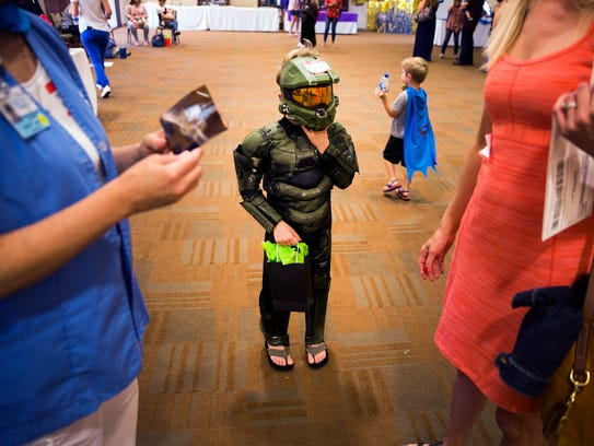 Ronan O'Connell, 6, adjusts his mask while his mom,