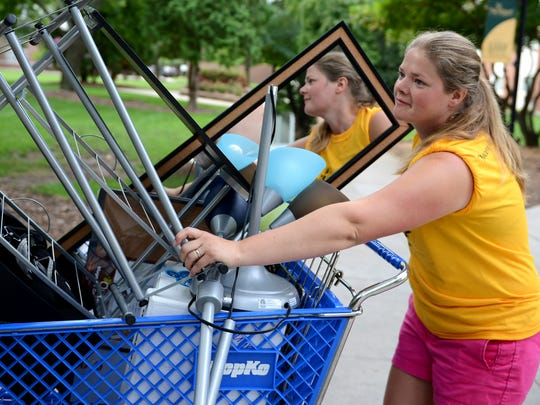 St. Norbert College staff member Jenifer Allen helps freshman students move belongings into Frank J. Sensenbrenner Hall on Thursday.