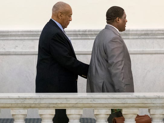 Bill Cosby escorted by one of his aides from the courtroom