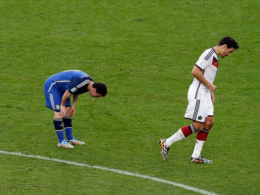 Argentina's Lionel Messi spits up as Germany's Mats Hummels walks by during the World Cup final soccer match between Germany and Argentina at the Maracana Stadium in Rio de Janeiro, Brazil, Sunday, July 13, 2014. (AP Photo/Themba Hadebe)