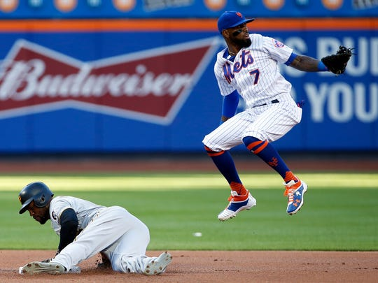 Pittsburgh Pirates' Starling Marte steals second base as New York Mets shortstop Jose Reyes (7) misses a throw during the first inning of a baseball game on Monday, June 25, 2018, in New York.
