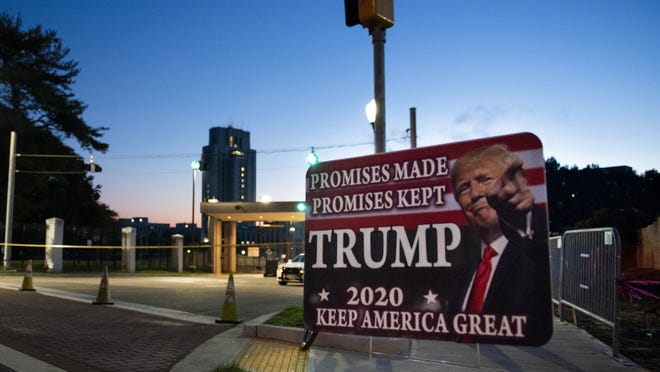 President Donald Trump drives past supporters gathered outside Walter Reed National Military Medical Center in Bethesda, Md., Sunday, Oct. 4, 2020. Trump was admitted to the hospital after contracting COVID-19.