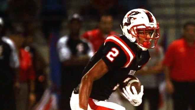 Palm Springs High School's Tayler Hawkins runs for yardage against Coachella Valley High School.