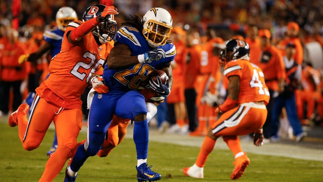 San Diego Chargers running back Melvin Gordon is brought down by Denver Broncos free safety Darian Stewart, left, and cornerback Chris Harris during the second half of an NFL football game Thursday, Oct. 13, 2016, in San Diego. (AP Photo/Lenny Ignelzi)