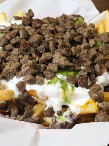 A platter of carne asada fries includes cheese, beans,