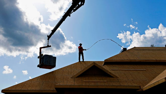 Chris Wallace delivers shingles bought from Roof Depot, the roofing supply company for whom Wallace works, to a house in the Shuyler Ridge subdivision in Republic on Tuesday.