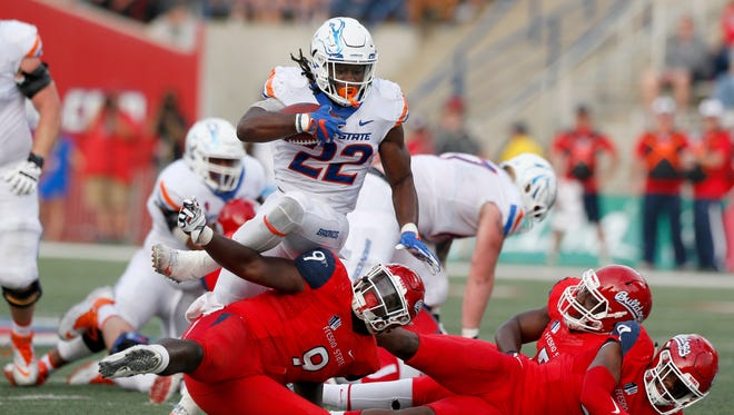 Boise State running back Alexander Mattison attempts to run over the top of Fresno State linebacker Jeffrey Allison during a game last season.
